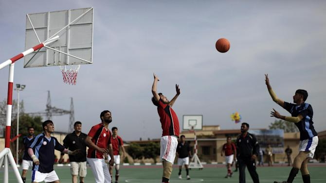 Disabled Pakistani soldiers play a basketball match during a sports competition, in Rawalpindi, Pakistan, Saturday, March 16, 2013. Dozens of wounded Pakistani troops, many of them maimed during the fighting in the country's tribal areas bordering Afghanistan, gathered Saturday for a sports competition designed to help them recover -- in body and spirit. (AP Photo/Muhammed Muheisen)