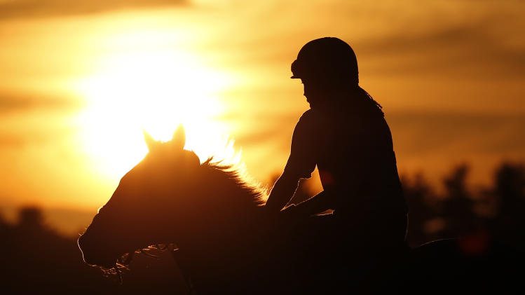 An exercise rider rides a horse during morning workouts at Saratoga Race Course in Saratoga Springs, N.Y., on Thursday, July 19, 2012. The 144th Saratoga horse racing season starts on Friday. (AP Photo/Mike Groll)