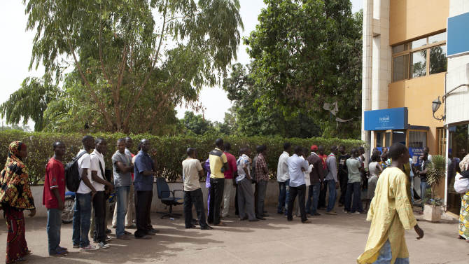 People stand in line outside a bank in Bamako, Mali Friday, March 30, 2012. Capt. Amadou Haya Sanogo, the junior officer who grabbed power in a coup, says he plans to hold free elections and to rapidly return Mali to its established order, but refused to give a timetable even as neighboring countries prepare to enact severe financial sanctions.(AP Photo/Rebecca Blackwell)