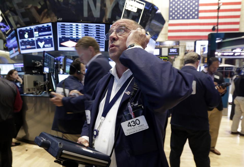 Trader Frederick Reimer, center, works on the floor of the New York Stock Exchange Friday, July 5, 2013. Robust hiring in the U.S. is boosting the stock market in early trading. (AP Photo/Richard Drew)