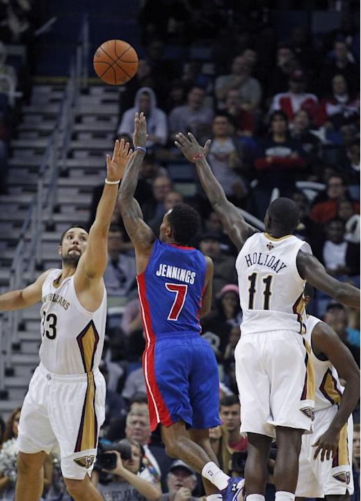 Detroit Pistons point guard Brandon Jennings (7) shoots between New Orleans Pelicans power forward Ryan Anderson (33) and point guard Jrue Holiday (11) in the second half of an NBA basketball game in