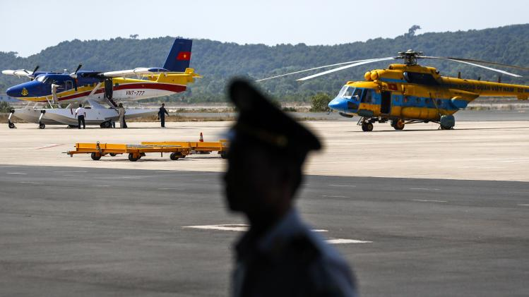 Officer stands guard near Vietnam aircraft before mission to find Malaysia Airlines flight MH370 that disappeared, at Phu Quoc Airport on Phu Quoc Island