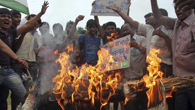 Indian protesters burn an effigy of Pakistani Prime Minister Nawaz Sharif during a protest in Ahmadabad, India, Saturday, Aug. 10, 2013. India's defense minister directly accused Pakistan on Thursday of killing five Indian soldiers in the disputed Himalayan region of Kashmir and suggested it could hurt peace efforts by the two countries. (AP Photo/Ajit Solanki)