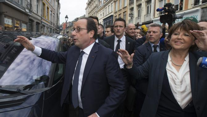 Lille's Mayor Martine Aubry and French President Francois Hollande walk in the streets after a lunch at a restaurant in the city centre in Lille