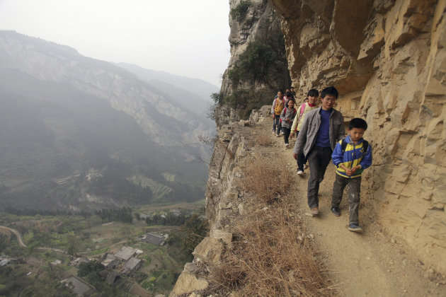 Xu Liangfan escorts students on a cliff path as they make their way to Banpo Primary School in Shengji county