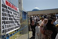 Muslim residents walk past signs displayed at the gate of Blue Mosque after attending a prayer mass in Maharlika village, Taguig city, south of Manila March 1, 2013. REUTERS/Romeo Ranoco