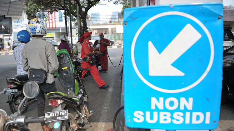 Motorists queue to fill their motorcycles with non-subsidized gasoline at a fuel station in Jakarta on August 29, 2014