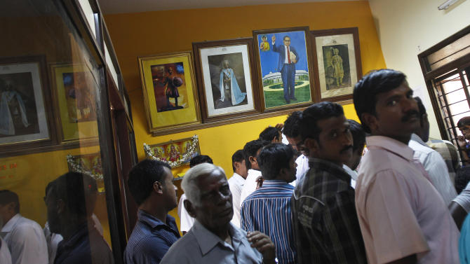 In this Dec. 10, 2012 photo, a portrait of Bhimrao Ramji Ambedkar, second right, a dalit leader and architect of the Indian Constitution, hangs on the wall inside the government registrar's office as people crowd to get their land registered, in Hoskote 30 kilometers (19 miles) from Bangalore in the southern Indian state of Karnataka. For years, Karnataka's land records were a quagmire of disputed, forged documents maintained by thousands of tyrannical bureaucrats who demanded bribes to do their jobs. In 2002, there were hopes that this was about to change. (AP Photo/Aijaz Rahi)