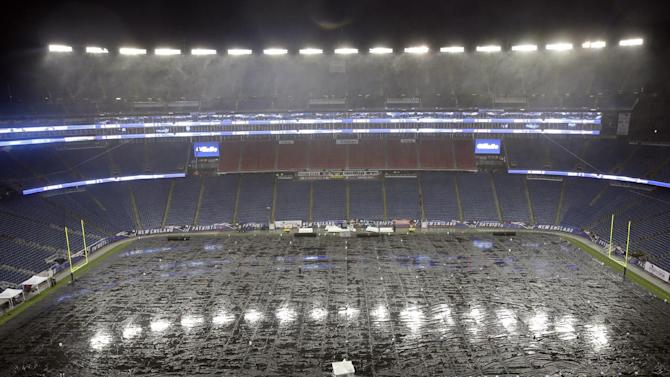 Rain falls on the tarp-covered field before an AFC divisional NFL playoff football game between the Indianapolis Colts and New England Patriots in Foxborough, Mass., Saturday, Jan. 11, 2014