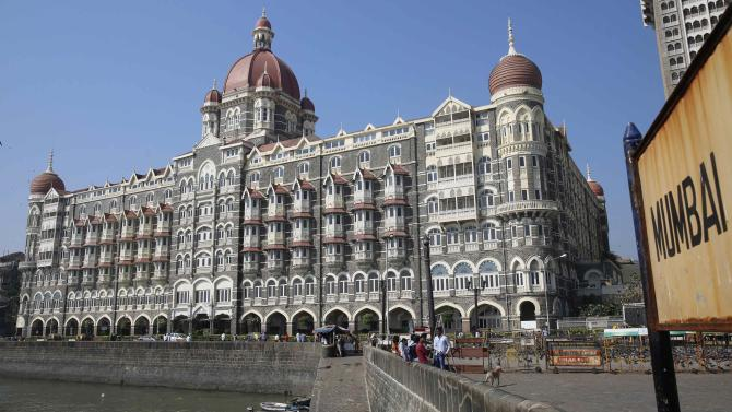 Tourists sit in front of the Taj Mahal hotel, which was one of the targets of the November 26, 2008 attacks, in Mumbai