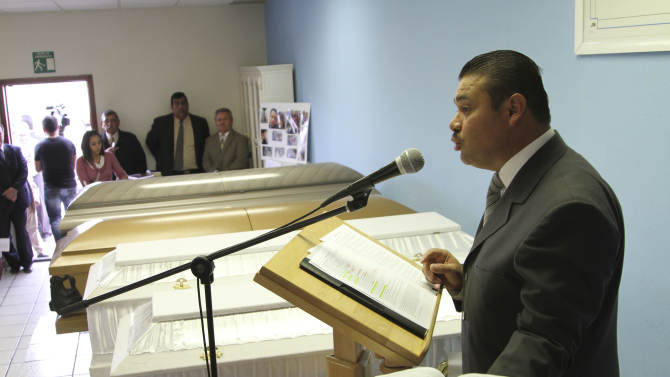 Jehova's Witness church elder Daniel Sierra delivers the eulogy for four of eight family members who were murdered on Sunday at Kingdom Hall in Ciudad Juarez, Mexico, Wednesday, Nov. 20, 2013. One of the suspects in the brutal stabbing deaths of a family of eight in this border city told journalists Wednesday that he stood guard outside the home as a second man detained in the case stabbed the victims to death in a dispute over a 1,500-peso ($115) dog-breeding debt. (AP Photo/Juan Carlos Llorca)