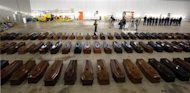 Coffins of victims from a shipwreck off Sicily are seen in a hangar of the Lampedusa airport October 5, 2013. REUTERS/Antonio Parrinello