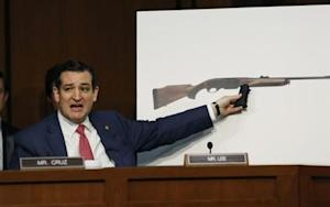 U.S. Senator Ted Cruz holds a plastic hand grip in front of a picture of a hunting rifle during Senate hearing in Washington