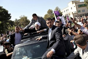 Iranian President Hassan Rouhani, center, waves to…