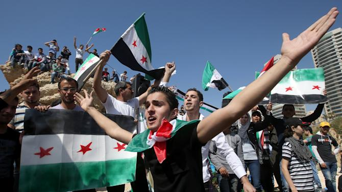 Syrian Kurdish citizens who live in Lebanon and are opposed to Syrian President Bashar Assad, shout slogans against the Syrian regime as others hold Syrian revolutionary flags, as they celebrate the Nowruz day, in Beirut, Lebanon, Thursday March 21, 2013.  Nowruz, the Farsi-language word for 'new year', is an ancient Persian festival, celebrated on the first day of spring in central Asian Republics, Afghanistan, Iran, Iraq and Turkey. (AP Photo/Hussein Malla)