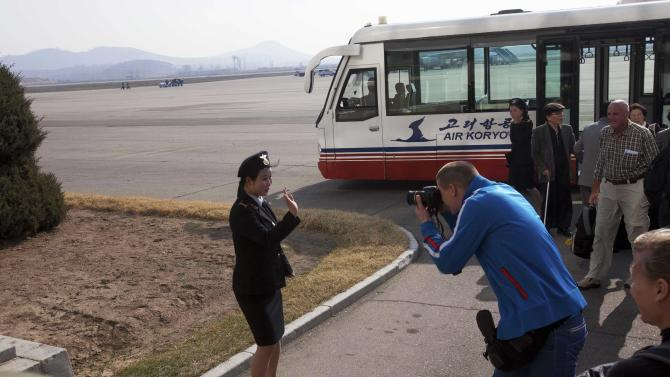 In this April 12, 2011 photo, a European tourist photographs a North Korean woman working at the airport as a North Korean Air Koryo flight arrives from Beijing, in Pyongyang, North Korea. (AP Photo/David Guttenfelder)
