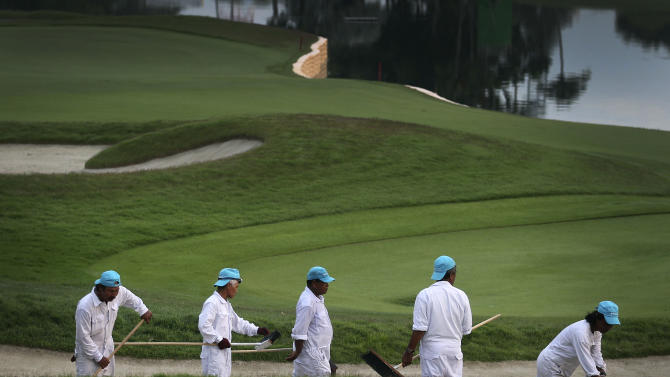 Workers prepare the golf course prior to the start of the Singapore Open golf tournament at the Serapong Course at Sentosa Golf Club in Singapore on Sunday, Nov. 11, 2012. (AP Photo/Wong Maye-E)