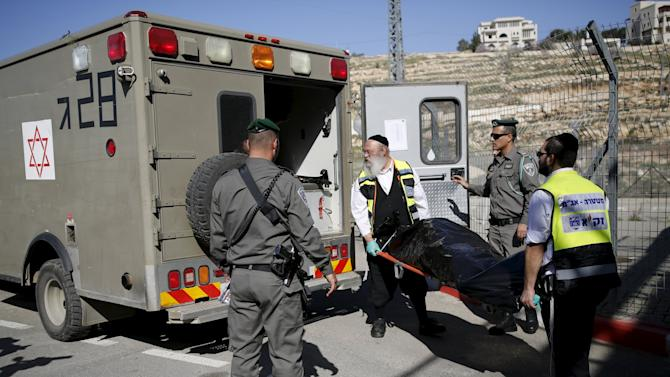 Israeli emergency service personnel evacuate the body of a Palestinian who was killed by Israeli troops after, police said, he tried to stab an Israeli paramilitary policeman at a checkpoint in the West Bank