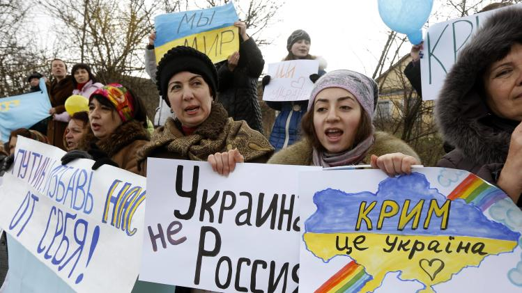 Participants hold placards and shout slogans during an anti-war rally in the Crimean village of Eskisaray