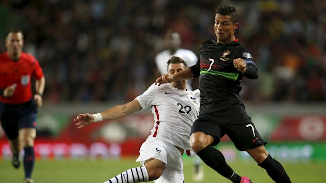 France's Morgan Schneiderlin fights for the ball with Portugal's Cristiano Ronaldo during their friendly soccer match at Alvalade stadium in Lisbon