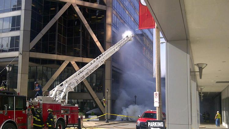 Firefighters work to put out fire at one of the largest office buildings in downtown St. Louis, Tuesday, June 25, 2013. The building has been evacuated afternoon after a series of explosions in the street outside. There were no reports of injuries from the explosions just before 5 p.m. Tuesday outside the One US Bank Plaza building, located across from the St. Louis Convention Center. (AP Photo/Jim Salter)