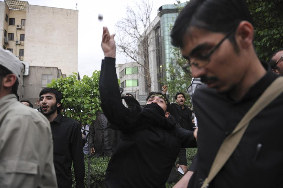 An Iranian demonstrator throws a stone at the Bahraini Embassy in Tehran, Iran, Saturday, April 30, 2011, in a gathering to show support for the Bahraini opposition. (AP Photo/IIPA,Sajjad Safari)