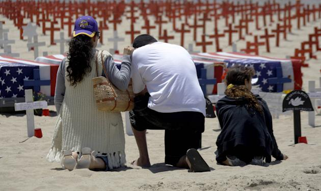 Visitors kneel at Arlington West, a Memorial Day display which uses crosses and other religious symbols to represent the service people killed in the Iraq and Afghanistan wars and is sponsored by Vete