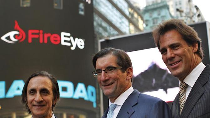 FireEye Inc. Chairman of the Board, DeWalt and Founder Aziz pose with Nasdaq CEO Greifeld outside the Nasdaq Market site in Times Square