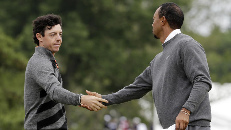 Rory McIlroy, left, of Northern Ireland, and Tiger Woods shake hands after putting on the 18th hole during the first round of the U.S. Open golf tournament at Merion Golf Club, Friday, June 14, 2013, in Ardmore, Pa. (AP Photo/Gene J. Puskar)