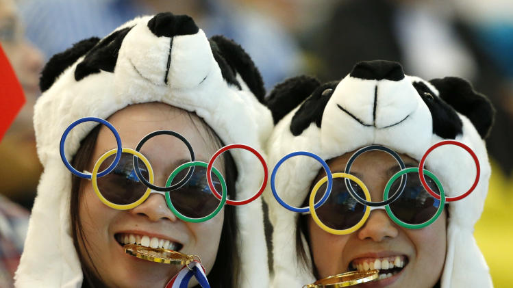 Two Chinese fans pause for photos prior to the Women's Synchronized 10 Meter Platform Diving final at the Aquatics Centre in the Olympic Park during the 2012 Summer Olympics, London, Tuesday, July 31, 2012. (AP Photo/Jae C. Hong)