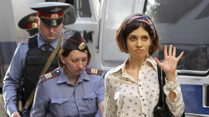 "Nadezhda Tolokonnikova, right, a member of feminist punk group Pussy Riot is escorted to a police van in Moscow, Russia, Wednesday, Aug. 1, 2012. Tolokonnikova and two other members of the group are facing trial on charges of hooliganism for performing a ""punk prayer"" at Moscow's main cathedral against Vladimir Putin's return to the Russian presidency. (AP Photo/Misha Japaridze)"