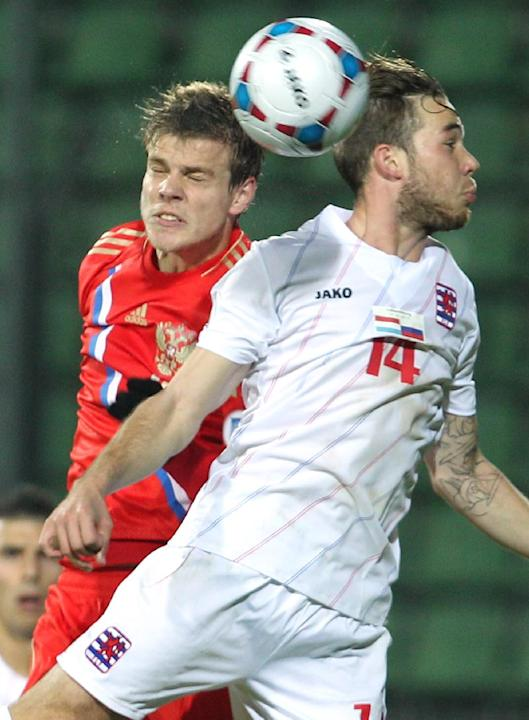 Luxembourg's Tom Laterza, right, is challenged by Russia's Alexander Kokorin, as they head for the ball, during their World Cup 2014 Group F qualifying soccer match in Luxembourg city, at the Josy Bar