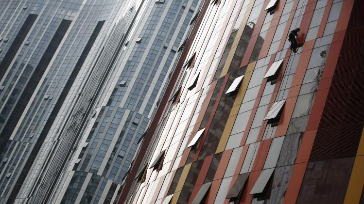 A worker cleans a window on a building at a business district in Beijing