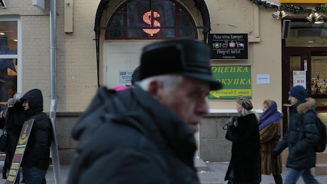 People walk in front of an exchange office in Moscow, Russia, Monday, Dec. 29, 2014. The Russian currency extended its losses on Monday after a report showed the economy has started shrinking in annual terms for the first time since 2009 as the country is buffeted by falling oil prices and Western sanctions.  (AP Photo/Ivan Sekretarev)