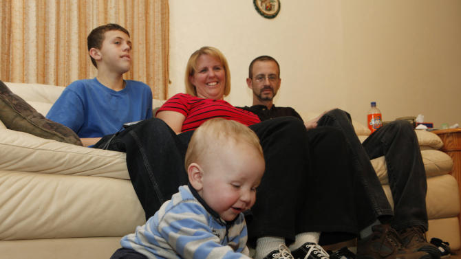 In this photo taken on Dec. 8, 2010, Coltyn, foreground, plays with a toy as his brother Austin, 12, mother Tracy and dad  Mike Hermanstorfer watch at their home in Colorado Springs, Colo.  Tracy Hermanstorfer, now 34, went into cardiac arrest while preparing to give birth to Coltyn at Memorial Hospital in Colorado Springs on Dec. 24, 2009.  Doctors quickly delivered Coltyn by emergency Cesarean section, but he appeared lifeless. Mike Hermanstorfer, who was at his wife's side when her heart stopped beating, thought he had lost both her and their newborn son. But doctors revived Coltyn as Hermanstorfer cradled him in his arms, and about 45 minutes later, a nurse told him his wife's pulse had inexplicably returned. (AP Photo/Ed Andrieski)