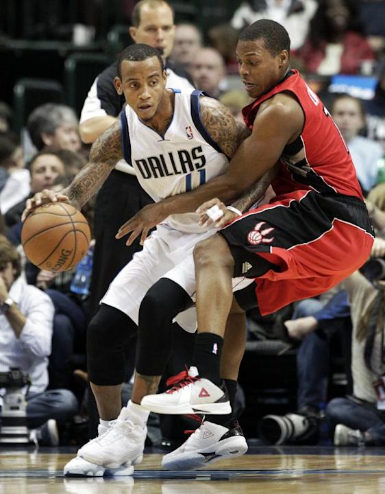 Dallas Mavericks' Monta Ellis (11) fights for position against Toronto Raptors' Kyle Lowry, right, in the first half of an NBA basketball game, Friday, Dec. 20, 2013, in Dallas