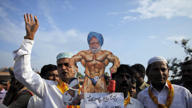 """Activists of Telugu Desam Party (TDP) carry a caricature of Indian Prime Minister Manmohan Singh with the words """"the blood suckers are not human beings but devils"""" during a protest at a bus station in Hyderabad, India, Thursday, Sept. 20, 2012. Angry opposition workers have disrupted train services as part of a daylong strike in India to protest rising diesel prices and the government's decision to open the country's huge retail market to foreign companies. (AP Photo/Mahesh Kumar A.)"""