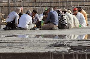 Foreign workers have a breakfast at a construction…