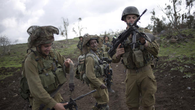 Israeli soldiers of the Golani brigade adjust their weapons during training near the border with Syria in the Israeli-controlled Golan Heights, Wednesday, Feb. 26, 2014. Hezbollah says Israel carried out an airstrike targeting its positions in Lebanon near the border with Syria earlier this week, claiming it caused damage but no casualties. The Wednesday statement was the group's first acknowledgement of the reported Monday night airstrikes. (AP Photo/Ariel Schalit)