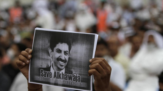 """A Bahraini anti-government protester raises a picture of jailed opposition human rights activist Abdulhadi al-Khawaja, on his 49th day of a hunger strike, during a demonstration Thursday, March 29, 2012, outside U.N. offices in Manama, Bahrain. Opposition societies organized Thursday's protest against security forces use of tear gas, which rights activists blame for about 30 deaths. Earlier this month, the U.N. human rights office in Geneva expressed its concern about the use of tear gas, citing """"worrying reports of the disproportionate use of force by Bahraini security forces."""" (AP Photo/Hasan Jamali)"""