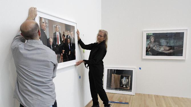 "Annie Leibovitz, right, helps Zak Kelley, of Columbus, hang one of her photographic prints before the opening of her exhibition at the Wexner Center for the Arts Friday, Sept. 21, 2012, in Columbus, Ohio. Leibovitz's exhibition features work from her ""Master Set,"" an authoritative edition of 156 images. (AP Photo/Jay LaPrete)"