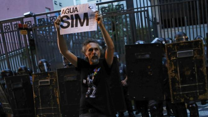 Demonstrator holds a sign, in reference to water rationing, in front of riot police during a protest against fare hikes for city buses, subway and trains, outside Sao Paulo Mayor's house in Sao Paulo