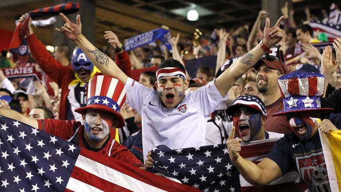 FILE - In a Jan. 21, 2012, file photo United States soccer fans celebrate a game-winning goal against Venezuela in the second half of a friendly soccer match in Glendale, Ariz. ESPN and Fox executives see devoted fans at Major League Soccer matches and figure burgeoning national television viewership is soon to follow. (AP Photo/Ross D. Franklin)