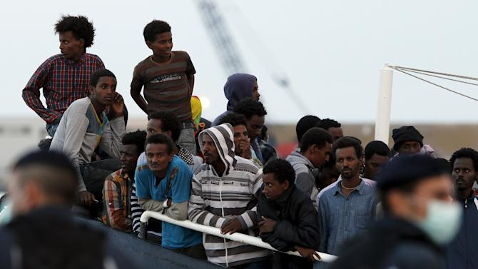 Migrants wait to disembark in the Sicilian harbour of Augusta