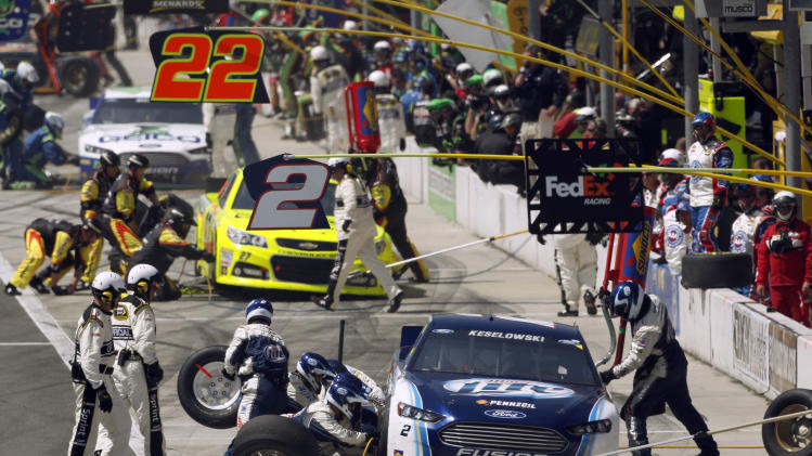 Brad Keselowski and other drivers pit during a caution flag in the NASCAR Sprint Cup Series auto race in Fontana, Calif., Sunday, March 24, 2013. (AP Photo/Reed Saxon)