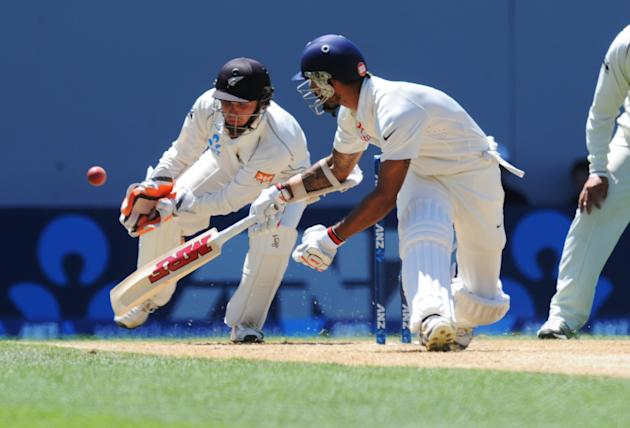 India's Shikar Dhawan, right, sweeps past New Zealand's wicket keeper BJ Watling on the fourth day of the first cricket test at Eden Park in Auckland, New Zealand, Sunday, Feb. 9, 2014. (AP Photo/SNPA