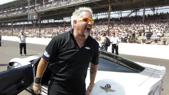 Celebrity chef and pace car driver Guy Fieri laughs as he stands next to the pace car before the start of the Indianapolis 500 auto race at the Indianapolis Motor Speedway in Indianapolis, Sunday, May 27, 2012. (AP Photo/Michael Conroy)