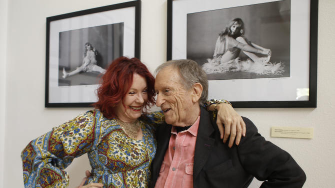 """In this photo taken Saturday, April 13, 2013 former Rolling Stone photographer Baron Wolman, right, embraces Pamela Des Barres, left, the subject in both photographs on the wall behind during the opening of Wolman's photo exhibit """"The Groupies"""" at Markham Vineyards in St. Helena, Calif.  More than 75 wineries have art on display all year long.  (AP Photo/Eric Risberg)"""