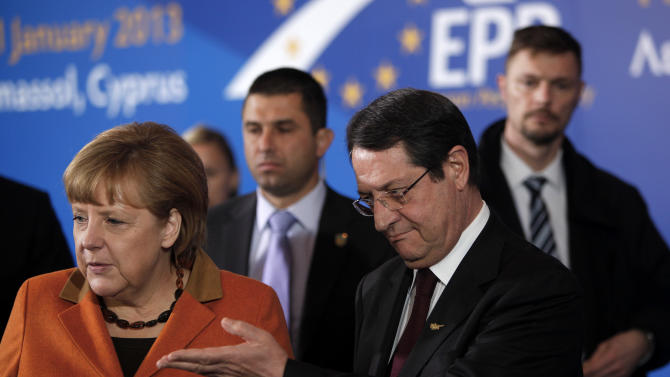 German Chancellor Angela Merkel and Cyprus' main opposition Democratic Rally party leader Nicos Anastasiades, right, are seen before a European People's Party (EEP) meeting in Cyprus' southern coastal resort of Limassol in an extraordinary summit on Friday, Jan. 11, 2013. Among the topics of discussion at the meeting hosted by the leader of Cyprus' main opposition Democratic Rally party Nicos Anastasiades will be the EU budget. Anastasiades is currently leading opinion polls as the top contender ahead of the country's Feb. 17 presidential election. Cyprus is in the midst of talks with international lenders on a bailout to rescue its ailing banking sector that sustained massive losses on bad Greek debt and loans. (AP Photo/Petros Karadjias)