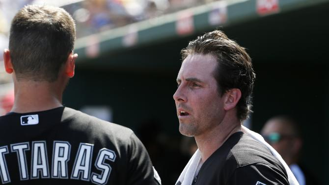 Chicago White Sox pitcher Scott Carroll, right, talks with catcher George Kottaras, left, in the dugout during the second inning of a spring training baseball game against the Cleveland Indians Sunday, March 29, 2015, in Goodyear, Ariz. (AP Photo/Ross D. Franklin)